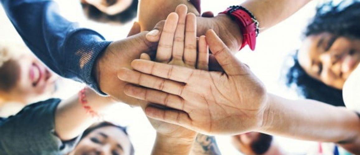 Flera människor lägger händerna på varandras händer.