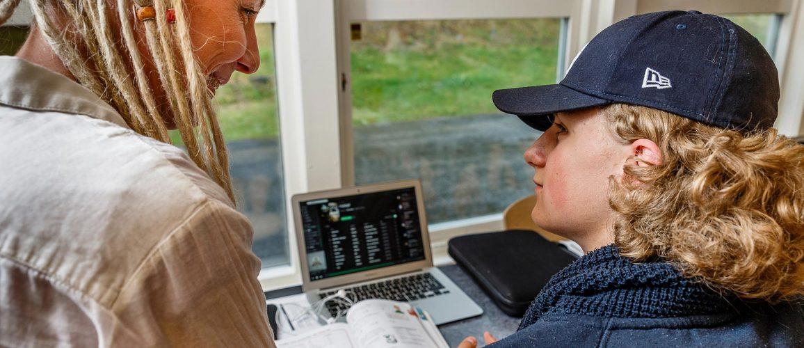 Tonårig kille interagerar med kvinna. På bordet framför dem finns en bärbar dator och en uppslagen bok.