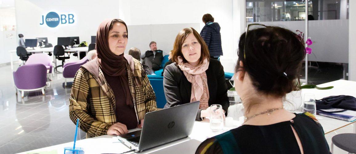 Tre kvinnor samtalar vid ett bord i kontorsmiljö. En av dem har en bärbar dator framför sig. Bakom dem sitter några personer i en soffa.