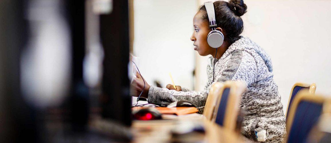 En ung kvinna med hörlurar sitter vid en datorskärm. Hon har en penna i sin hand.